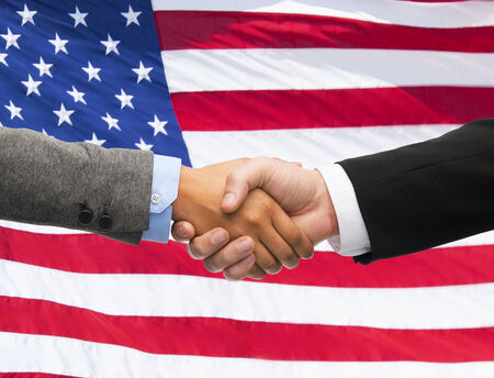 union flag: partnership, politics, gesture and people concept - close up of handshake over american national flag background