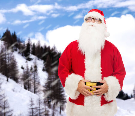 christmas, holidays and people concept - man in costume of santa claus over snowy mountains background photo