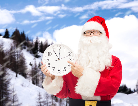 christmas, holidays and people concept - man in costume of santa claus with clock showing twelve pointing finger over snowy mountains background photo