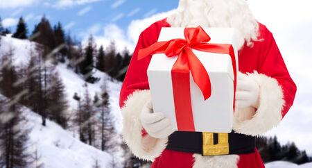christmas, holidays and people concept - close up of santa claus with gift box over snowy mountains photo