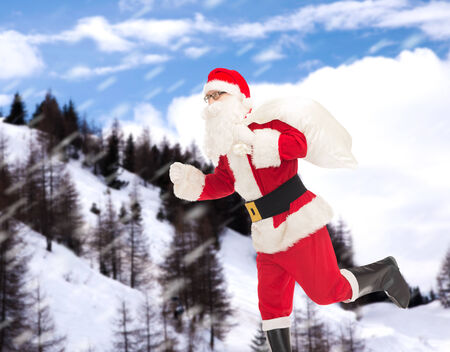 christmas, holidays and people concept - man in costume of santa claus running with bag over snowy mountains background photo