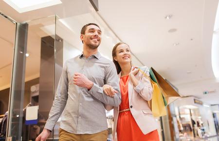 novio: venta, el consumismo y el concepto de la gente - la feliz pareja joven con bolsas de compras caminando en mall
