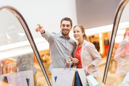sale, consumerism and people concept - happy young couple with shopping bags rising on escalator and pointing finger in mall