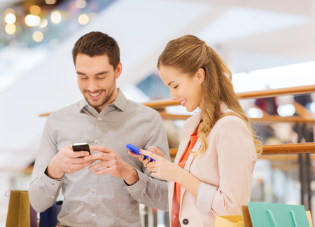 latin looking: sale, consumerism, technology and people concept - happy young couple with shopping bags and smartphones in mall
