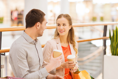 consumerism: sale, shopping, consumerism, leisure and people concept - happy couple with shopping bags drinking coffee from paper cups in mall