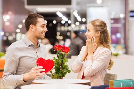 romans: miłość, romans, Walentynki, para i koncepcja ludzie - szczęśliwy młody człowiek z czerwone kwiaty podając obecnych do uśmiechnięta kobieta w kawiarni w centrum handlowym