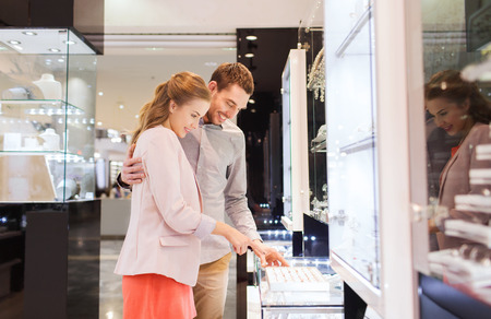sale, consumerism, shopping and people concept - happy couple choosing engagement ring at jewelry store in mall Stock Photo
