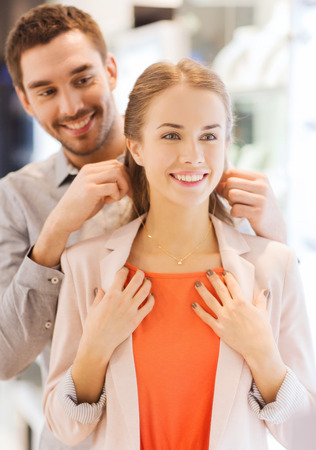 sale, consumerism, presents, holidays and people concept - happy couple trying golden pendant on at jewelry store in mall