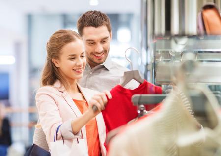 販売、消費者と人々 のコンセプト - モールでのショッピング バッグを選択すると幸せな若いカップル ドレスします。