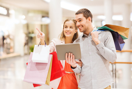 satisfied people: sale, consumerism, technology and people concept - happy young couple with shopping bags and tablet pc computer pointing finger in mall