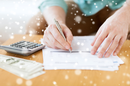 accountancy: savings, finances, paperwork and people concept - close up of man with calculator counting money and making notes at home Stock Photo
