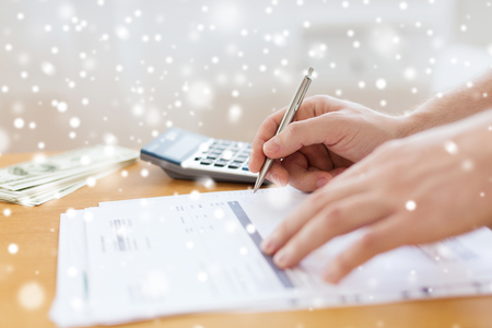 declaration: savings, finances, paperwork and people concept - close up of man with calculator, money and papers doing tax report at home