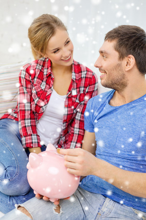 thrifty: money, home, finance and relationships concept - smiling couple with piggybank sitting on sofa Stock Photo