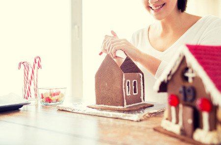christmas cooking: cooking, people, christmas and decoration concept - happy woman making gingerbread houses at home