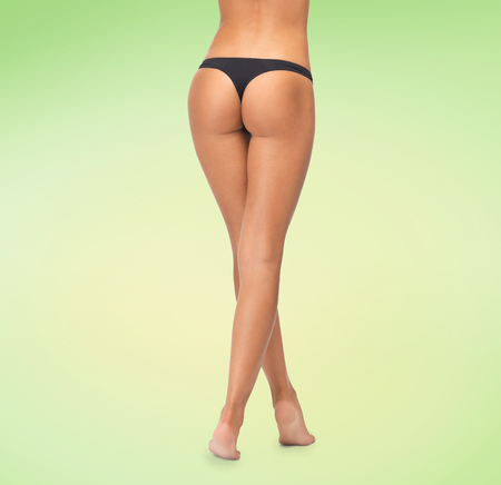 black ass: beauty, people and bodycare concept - close up of female legs in black bikini panties over green background