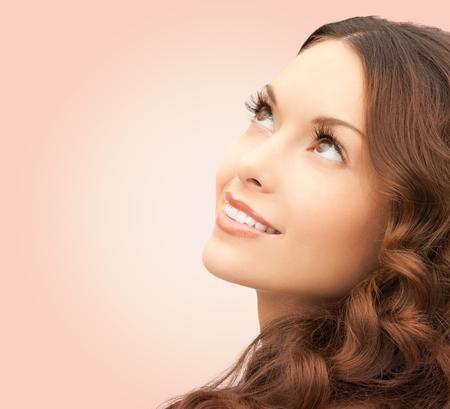 schoonheid, mensen en gezondheidsconcept - mooie jonge vrouw die omhoog over roze achtergrond kijkt