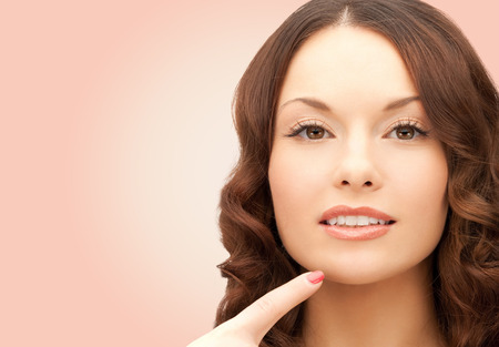 touching face: beauty, people and health concept - beautiful young woman pointing finger to her chin over pink background
