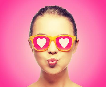 felicidad: amor, la felicidad, el día de san valentín, expresiones faciales y concepto de la gente - retrato de adolescente en gafas de sol de color rosa con corazones beso que sopla