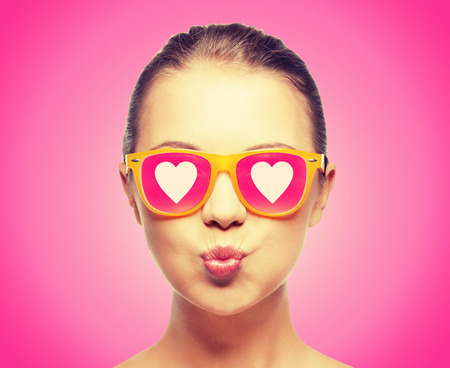 woman blowing: love, happiness, valentines day, face expressions and people concept - portrait of teenage girl in pink sunglasses with hearts blowing kiss