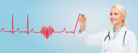 healthcare, medical and technology concept - young female doctor drawing heartbeat cardiogram in the air over blue background photo