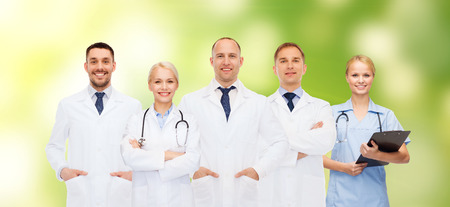 healthcare, people and medicine concept - group of doctors with stethoscopes and clipboard over green background photo