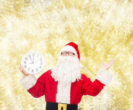 twelve month old: christmas, holidays and people concept - man in costume of santa claus with clock showing twelve over yellow lights background