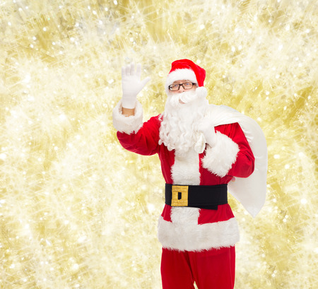 christmas, holidays, gesture and people concept - man in costume of santa claus with bag waving hand over yellow lights background photo