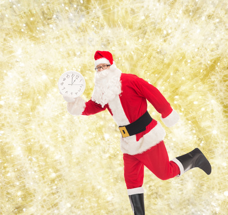 twelve month old: christmas, holidays and people concept - man in costume of santa claus running with clock showing twelve over yellow lights background