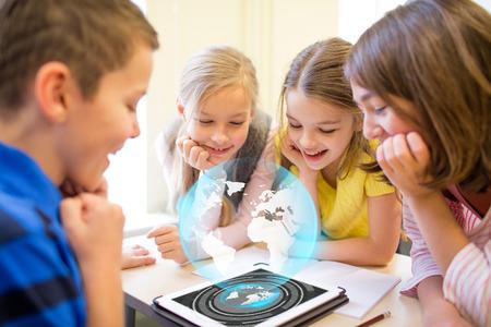 教育、小学校、学習、技術、人々 の概念 - 教室で休憩にグローブ ホログラムとタブレット pc のコンピューターの画面を探して学校の子供たちのグ