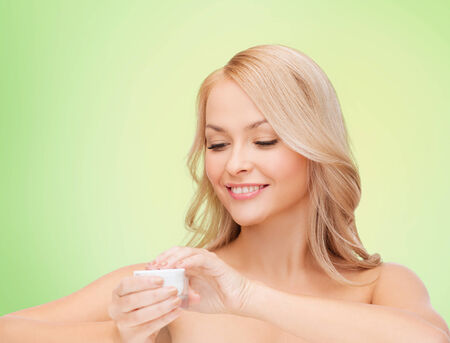 anti aging: health, beauty and spa concept - smiling young woman opening cream over green background