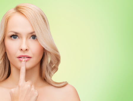 cold sore: health, people and beauty concept - beautiful young woman touching her lips over green background