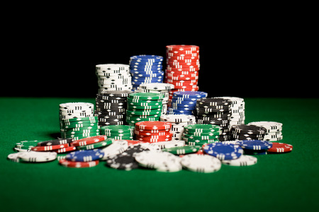 poker: gambling, fortune, game and entertainment concept - close up of casino chips on green table surface Stock Photo