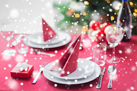 holidays, celebration and home concept - close up of room with christmas tree, small gift box and decorated table photo