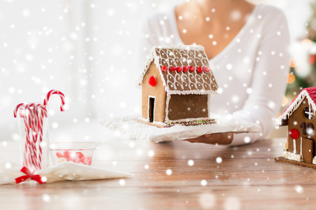 cooking, people, christmas and baking concept - close up of happy woman holding and showing gingerbread house at home photo