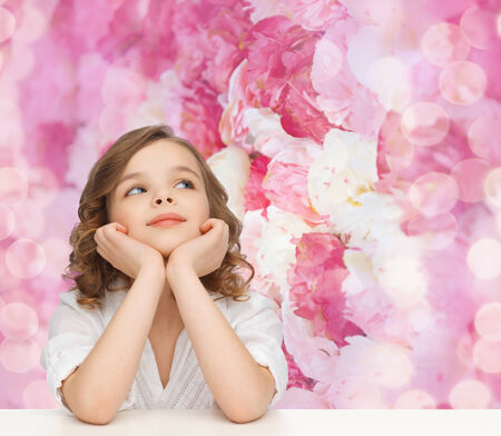 pre adolescent girl: children, childhood, holidays and happy people concept - beautiful girl sitting at table, looking up and dreaming over pink floral background Stock Photo