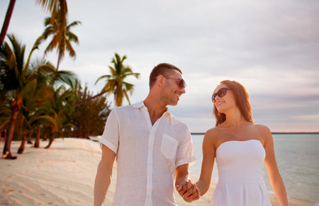 love, people, travel, summer and relations concept - smiling couple wearing sunglasses walking outdoors over tropical beach background photo