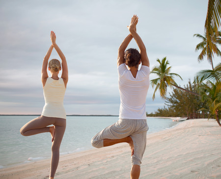 back training: fitness, sport, and lifestyle concept - couple making yoga exercises on beach from back