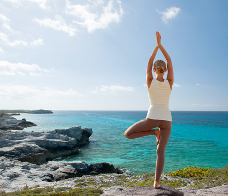 fitness, sport, people and lifestyle concept - young woman making yoga exercises on beach from back