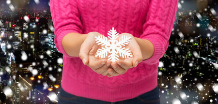 christmas, winter, holidays and people concept - close up of woman in pink sweater holding snowflake decoration over snowy night city background photo