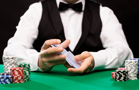 Casino, Glücksspiel, Poker, Menschen und Entertainment-Konzept - Nahaufnahme von Holdem Händler Mischen von Spielkarten Deck und Chips am grünen Tisch
