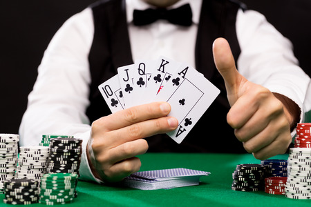 lear: casino, gambling, poker, people and entertainment concept - close up of poker player with playing cards and chips at green casino table