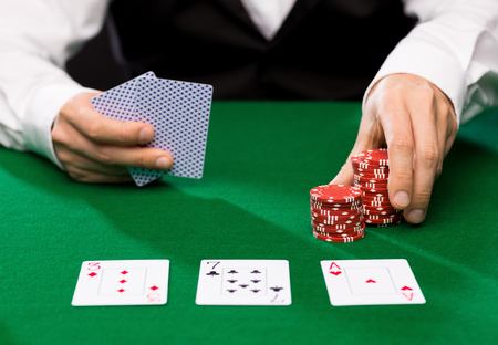 holdem: casino, gambling, poker, people and entertainment concept - close up of holdem dealer with playing cards and chips on green table