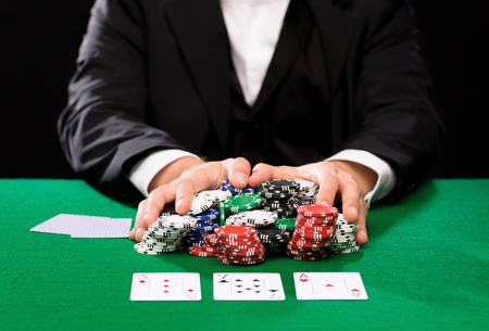 casino, gambling, poker, people and entertainment concept - close up of poker player with playing cards and chips at green casino table 版權商用圖片 - 34814805