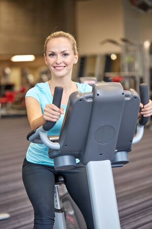 sport, fitness, lifestyle, technology and people concept - smiling woman exercising on exercise bike in gym photo