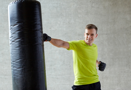fighting arts: sport, box and people concept - smiling young man in gloves boxing with punching bag in gym