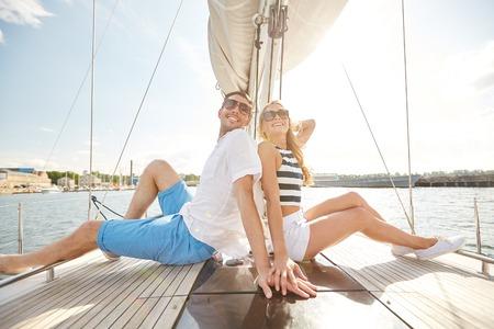 gente feliz: vacaciones, viaje, mar, la amistad y la gente concepto - sonriente pareja sentada y hablando en la cubierta del yate Foto de archivo