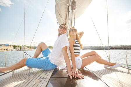 boat: vacation, travel, sea, friendship and people concept - smiling couple sitting and talking on yacht deck