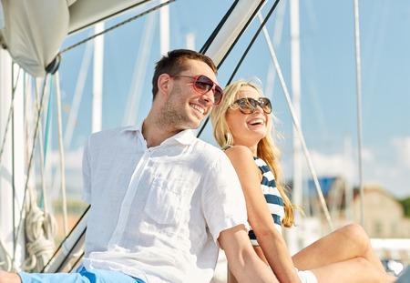 休暇、旅行、海、友情および人々 のコンセプト - カップル座り、ヨットのデッキで話して笑顔
