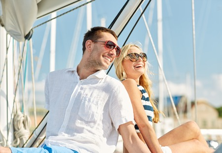 sail ship: vacation, travel, sea, friendship and people concept - smiling couple sitting and talking on yacht deck