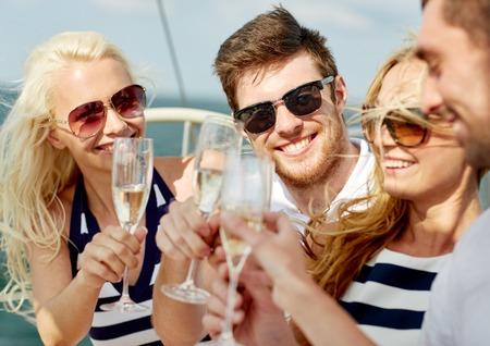 bebiendo vino: vacaciones, viaje, mar, la amistad y la gente concepto - amigos sonrientes con copas de champán en el yate Foto de archivo